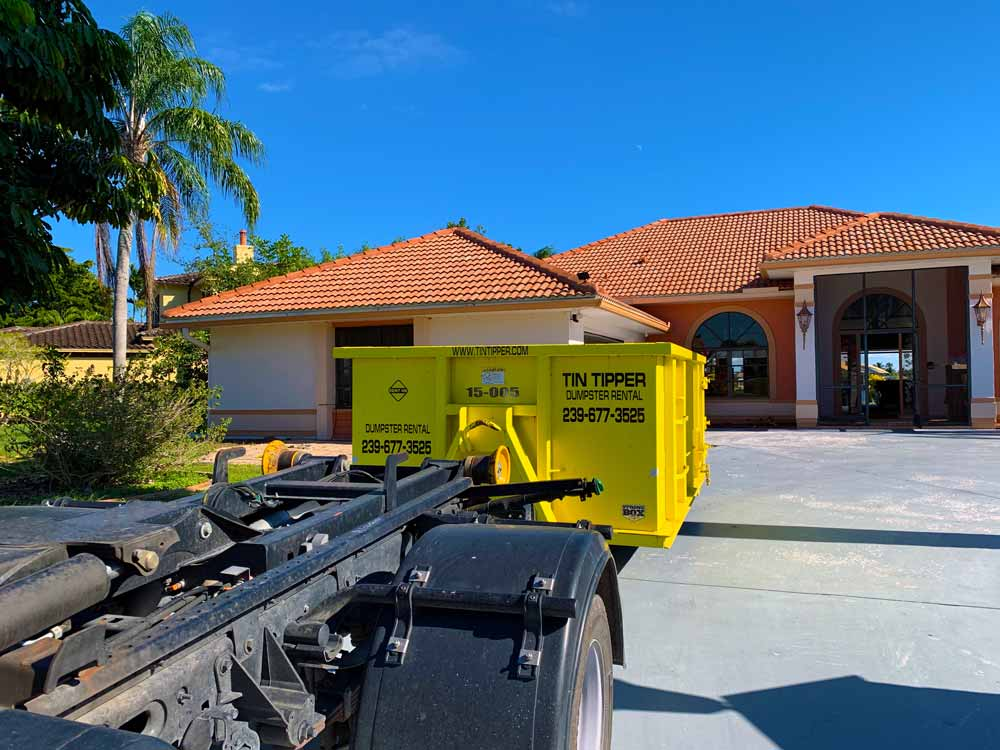 Dumpster-dropped-off-in-cape-coral,-Florida-placed-on-board-to-protect-the-homeowners-driveway-by-Tin-Tipper
