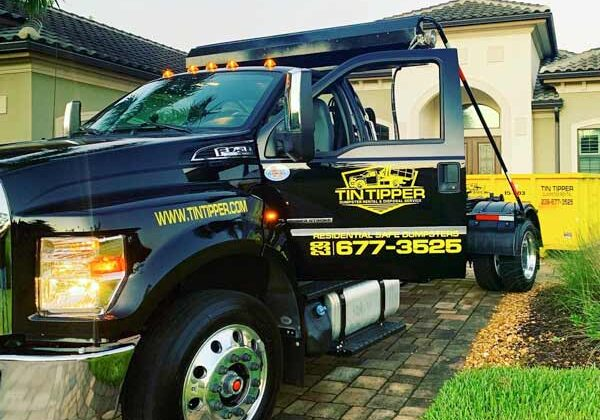 bin-container-tin-tipper-hoolift-truck-delivering-a-dumpster-to-a-property-in-cape-coral-florida